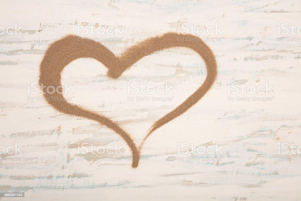 hearth shape of sea sand on a vintage wooden background zbiór zdjęć royalty-free