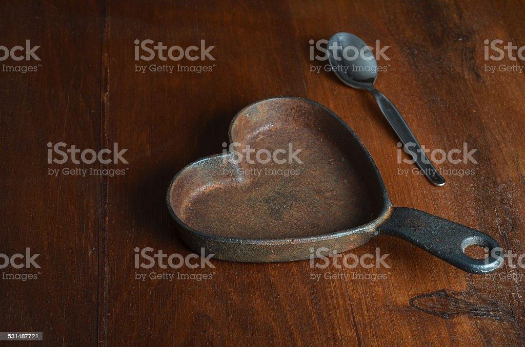 hearth shaped iron saucepan with silver tea spoon on wood stock photo