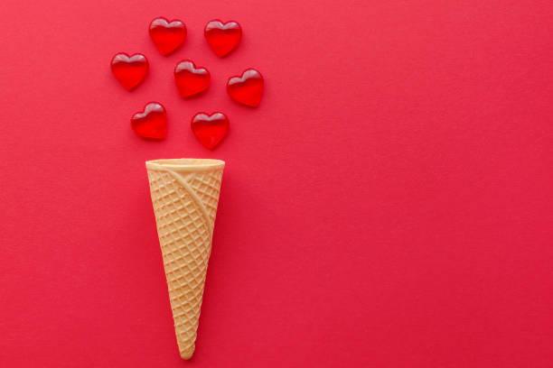 Herzen und Eis Waffel kegeln auf rotem Hintergrund mit Kopierraum – Foto