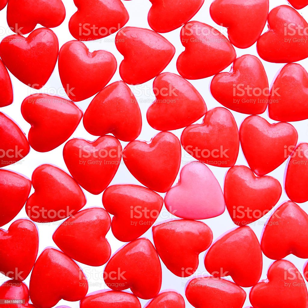 Hearts background. Pink heart between pile of red hearts stock photo