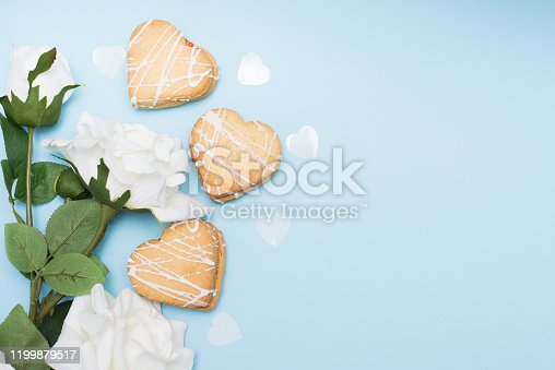 Hearts cookies with white Rose on blue background, flat lay, copy space