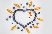 A heart's frame from mandarin pieces and blueberry on white background. A composition of the mandarin pieces and berries in form a heart. Beautiful frame and full of the vitamins