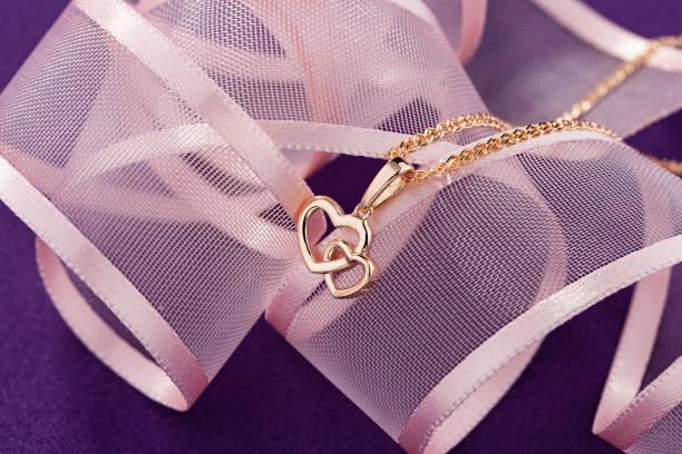 Hearts shape rose gold pendant necklace on pink background stock photo