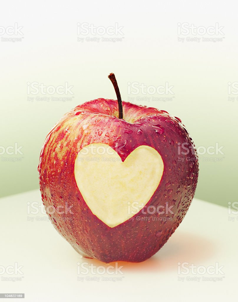 Heart-shape cut from side of red apple stock photo
