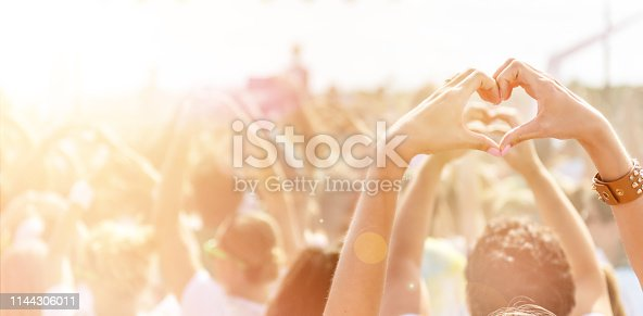 Woman making a heart-shape symbol for her favorite band at music festival in the crowd of young people.