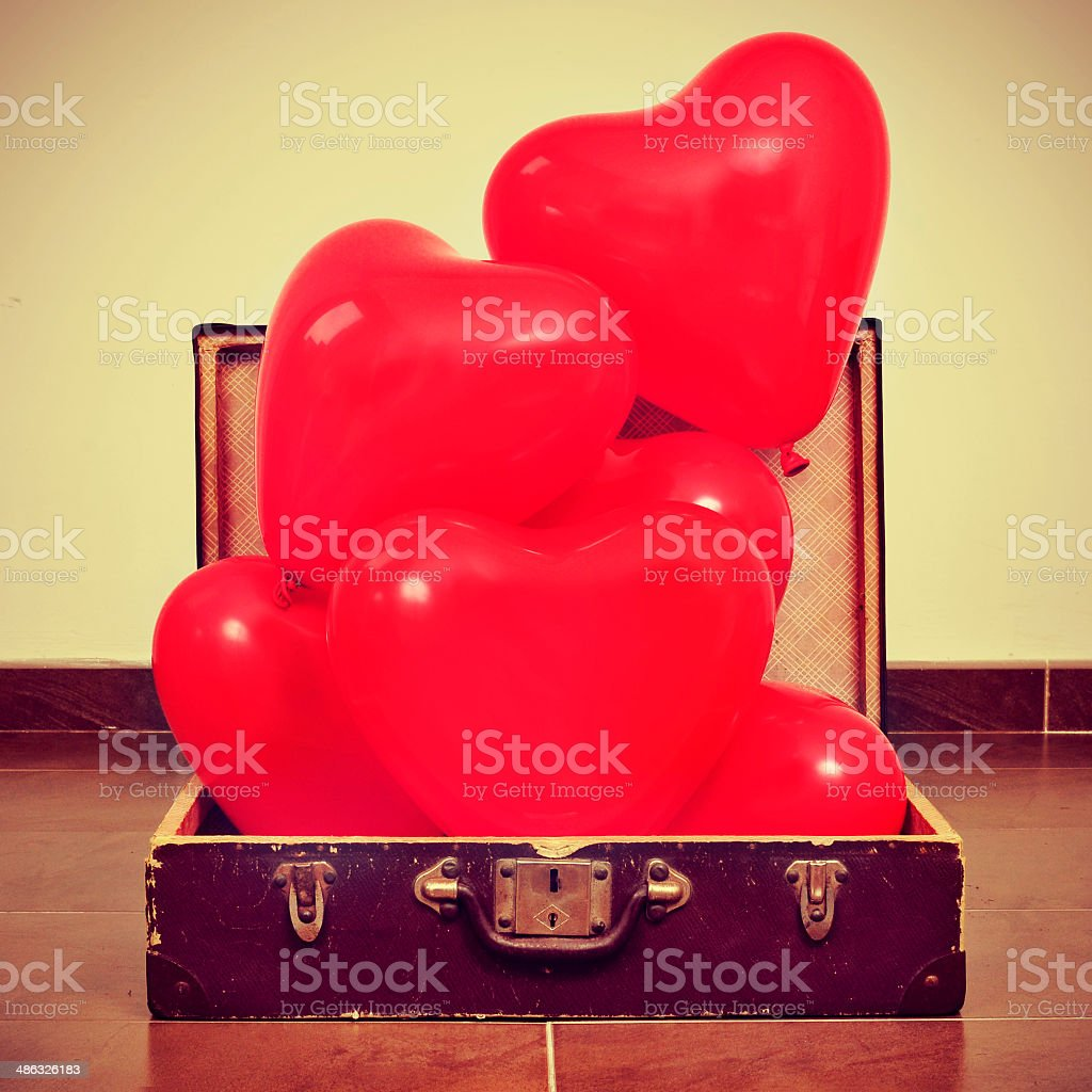 heart-shaped balloons in an old suitcase stock photo