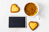 Heart-shaped biscuits and coffee on a wooden background. Place for text.Romantic breakfast. Greeting card for St. Valentine's Day.