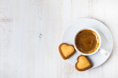 Heart-shaped biscuits and coffee on a wooden background. Romantic breakfast. Greeting card for St. Valentine's Day.