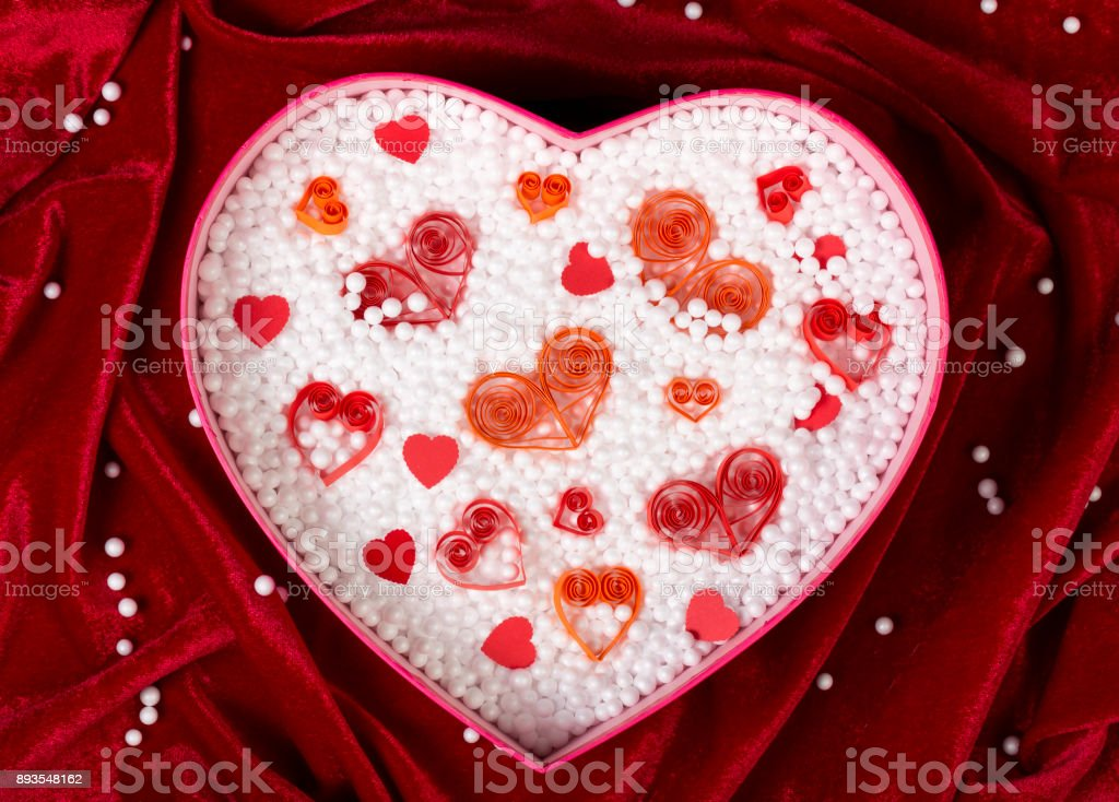 Heart-shaped box filled with small foam balls and handmade paper hearts on red velvet tablecloth. Top view. stock photo