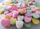 Heart-shaped candies form a Valentine, rose background (conversation hearts)