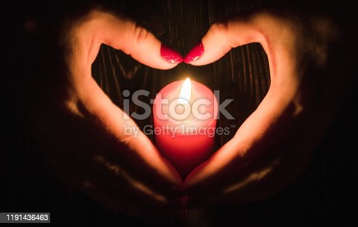 Heart-shaped female hands around  burning red candle