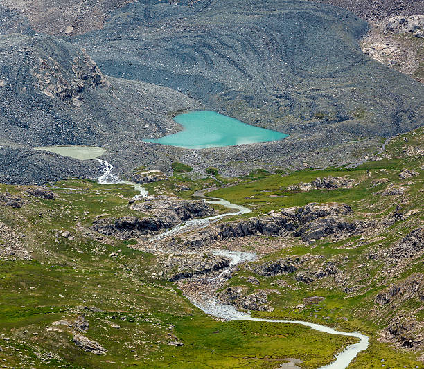 Heart-shaped lake and river flowing from glacier stock photo