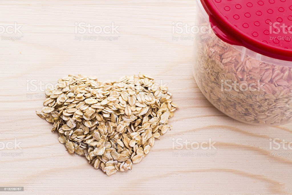 Heart-shaped oatmeal on wooden background stock photo