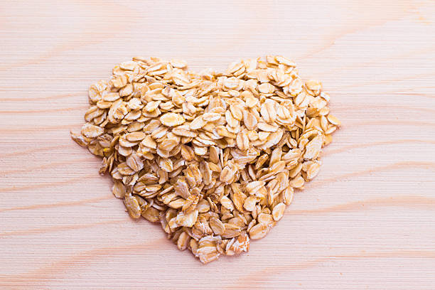 heart-shaped oatmeal on wooden background - 溶解 個照片及圖片檔