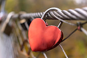 Red love lock hanging on the bridge