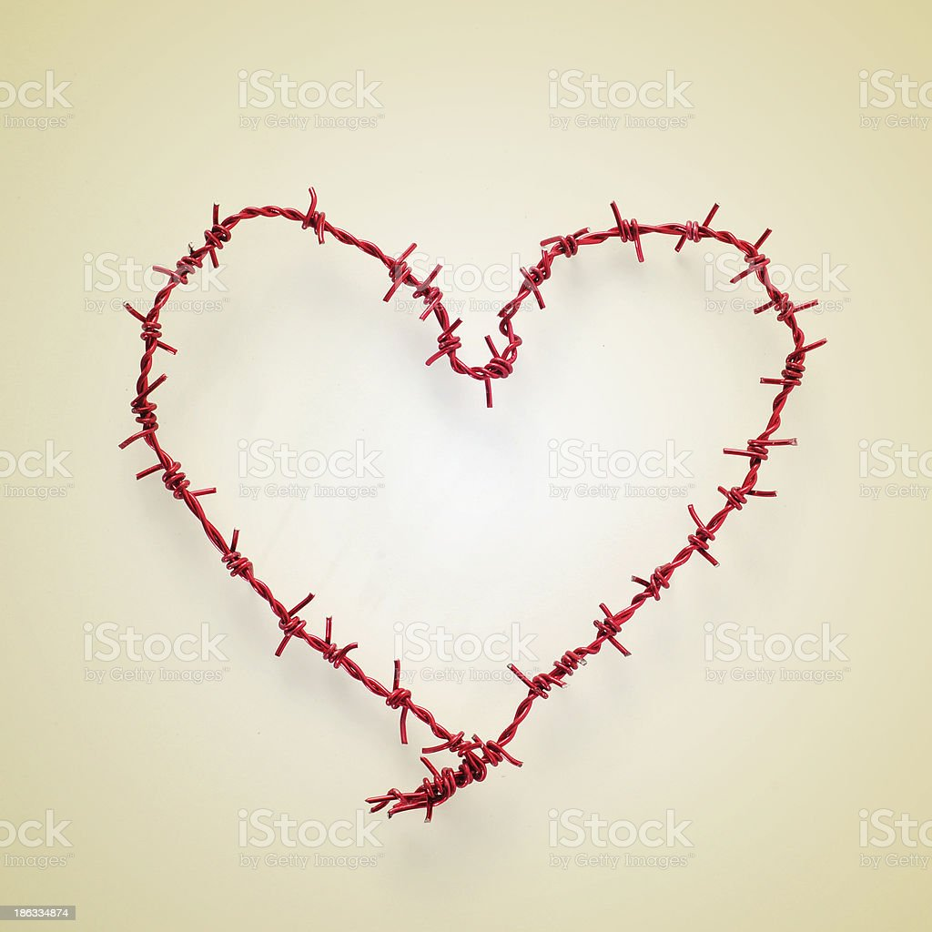 heart-shaped roll of barbed wire stock photo