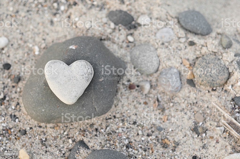 Heart-Shaped Stone with Other Rocks on Beach Sand royalty-free stock photo