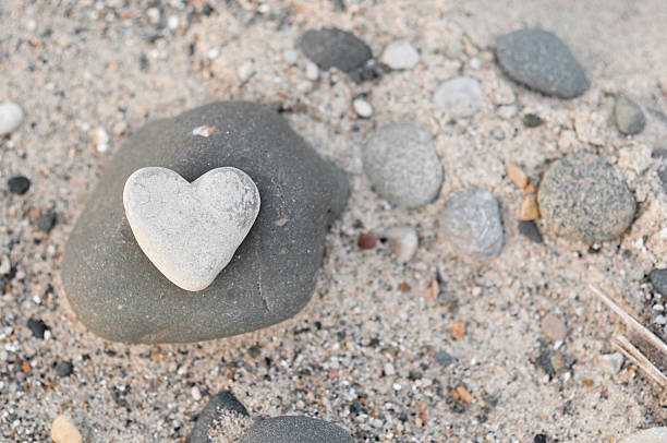 Heart-Shaped Stone with Other Rocks on Beach Sand stock photo