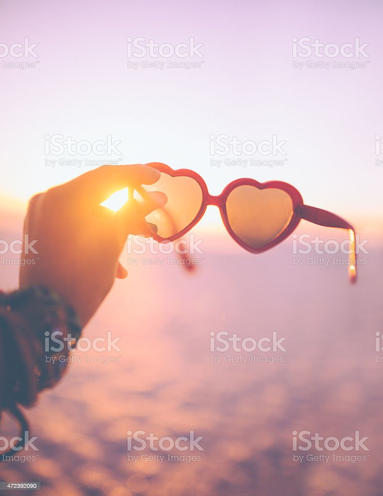 Heart-shaped sunglasses being held with a sunset behind stock photo