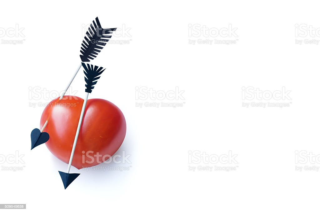 Heart-shaped tomato with two toothpick arrows. White copy-space background. stock photo