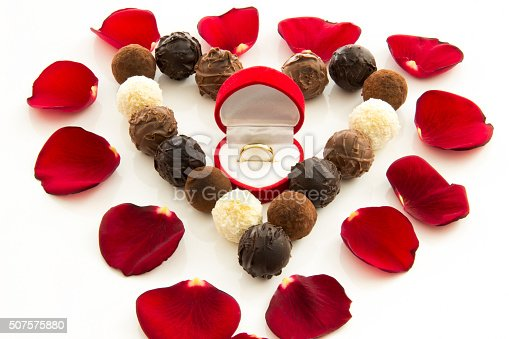 istock Heart-shaped truffles and wedding ring among rose petals 507575880