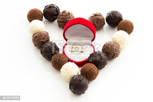 istock Heart-shaped truffles and wedding ring on white background 507575334