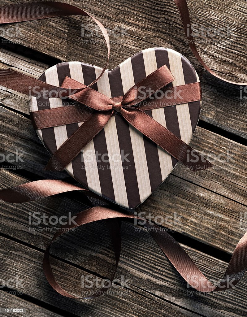 Heart-shaped Valentines Day gift box on wooden plates. royalty-free stock photo