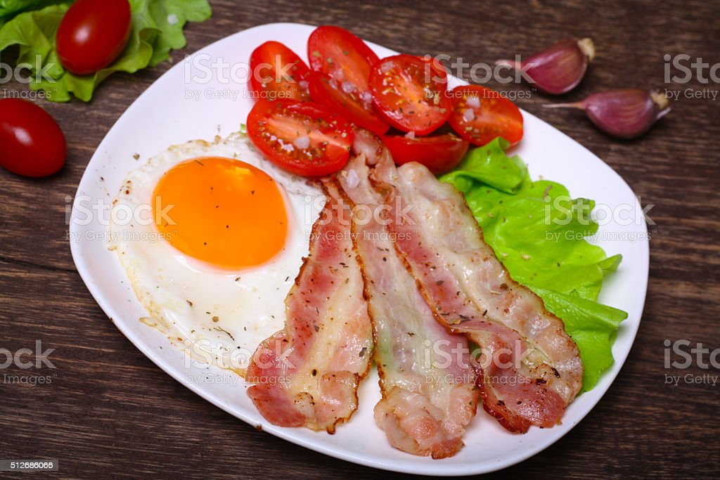 Hearty breakfast. Fried egg with bacon and tomatoes stock photo