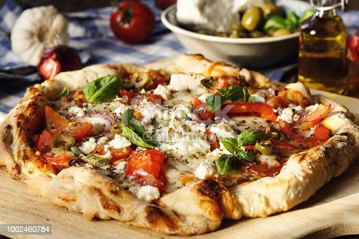 Hearty Greek Style Pizza with Feta Cheese, red onions, tomatoes, olives, garlic and herbs