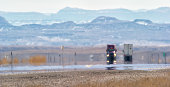 istock Heat Haze Distorts Video of Semi-Trucks Driving Down a Utah Interstate Surrounded by Mountains on a Sunny Day 1222084346