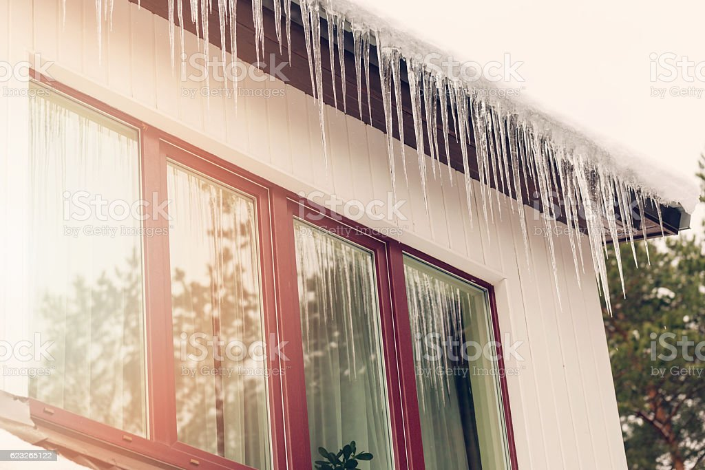 heat loss - icicles hanging on house roof stock photo