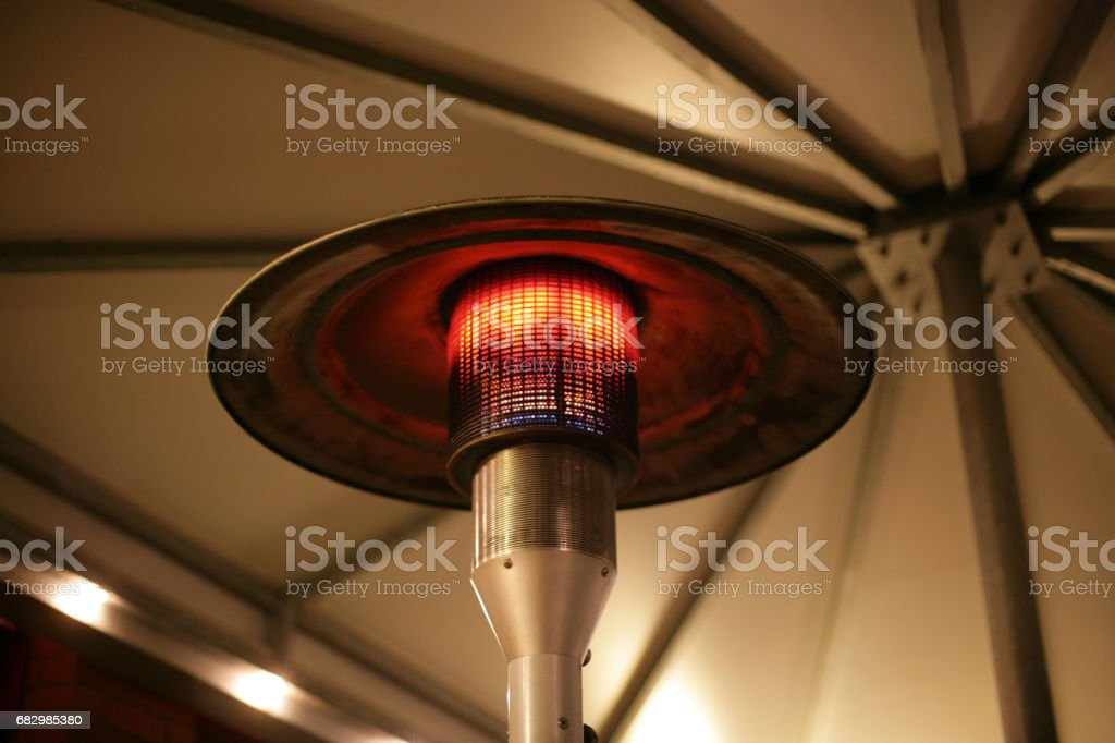 upper view on a heat lamp producing warmth in an outside part of the...