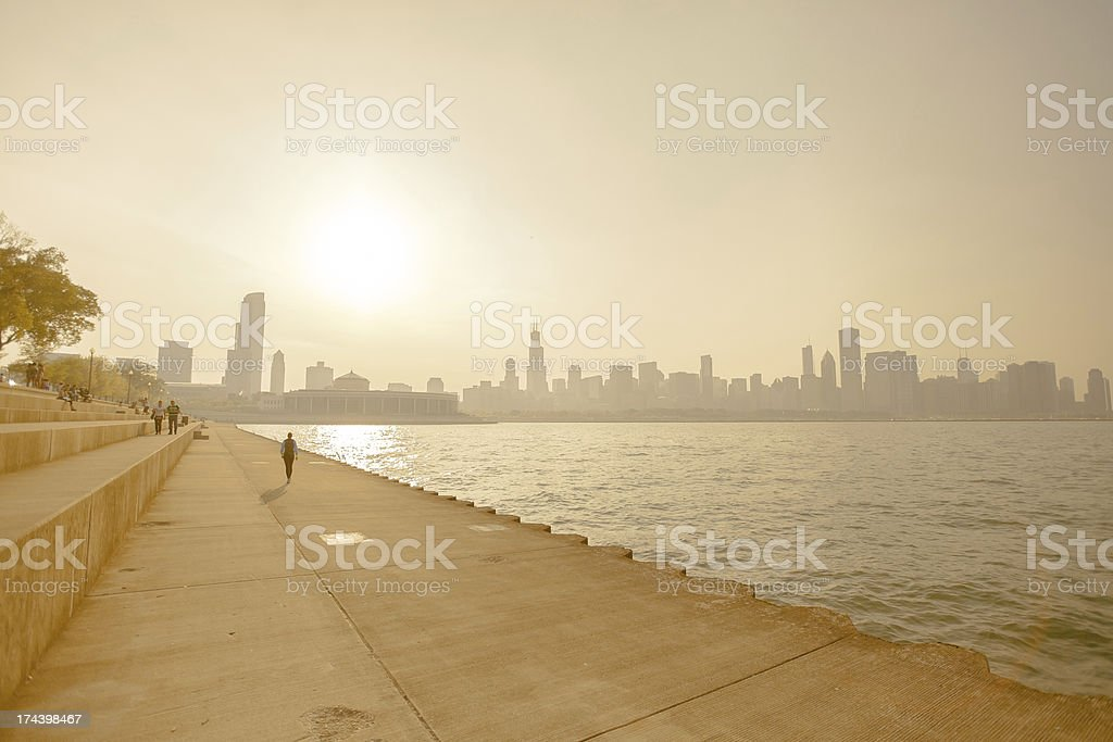 A heat wave and smog on the shoreline of a cityscape People walk along the lake near Chicago on a hot summer day Backgrounds Stock Photo