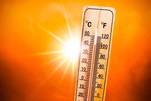 Background for a hot summer or heat wave, orange sky with with bright sun and thermometer