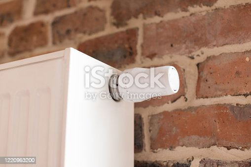 A white heater with a knob on  brick wall