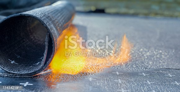 Close-up of heating and melting of bitumen rolls.