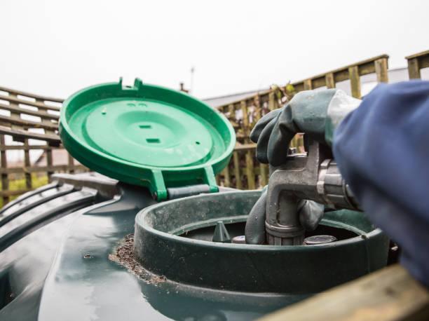 verwarming olie levering, mondstuk geplaatst in olietank te vullen - brandstoftank stockfoto's en -beelden