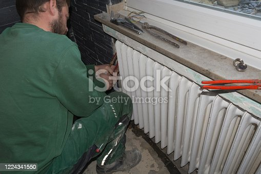 Plumbing or heating plumber dismantles an old finned tube radiator