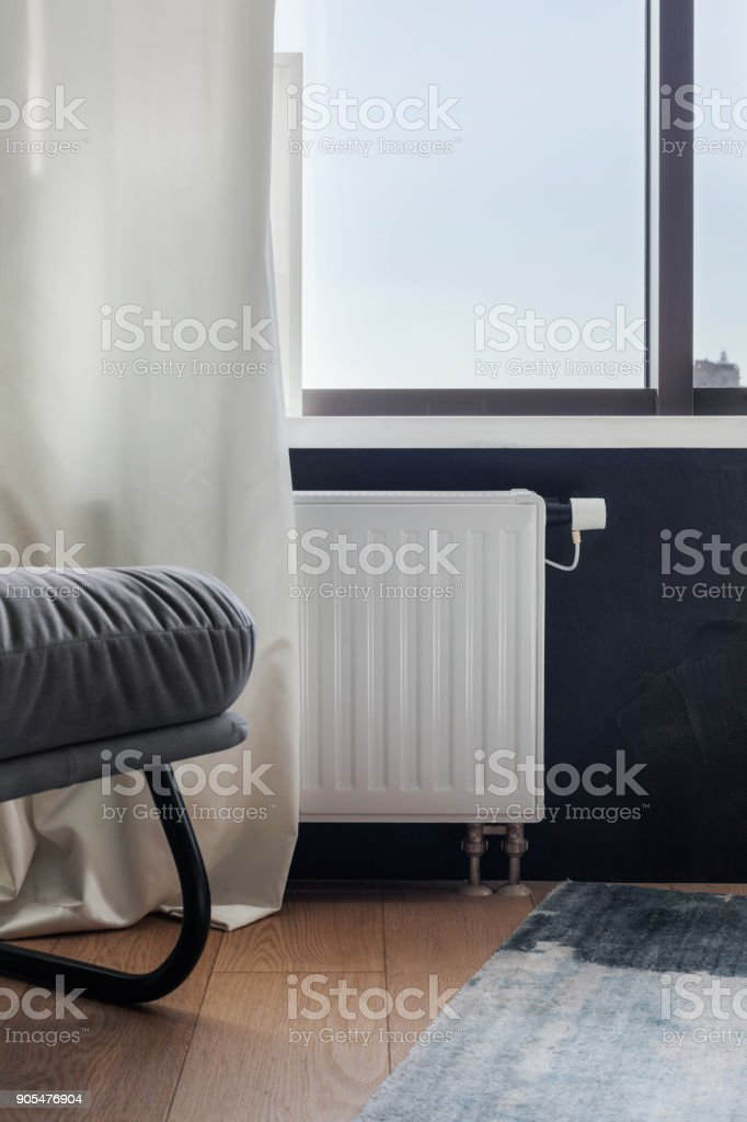 Heating white radiator with adjuster of warming in living room. stock photo