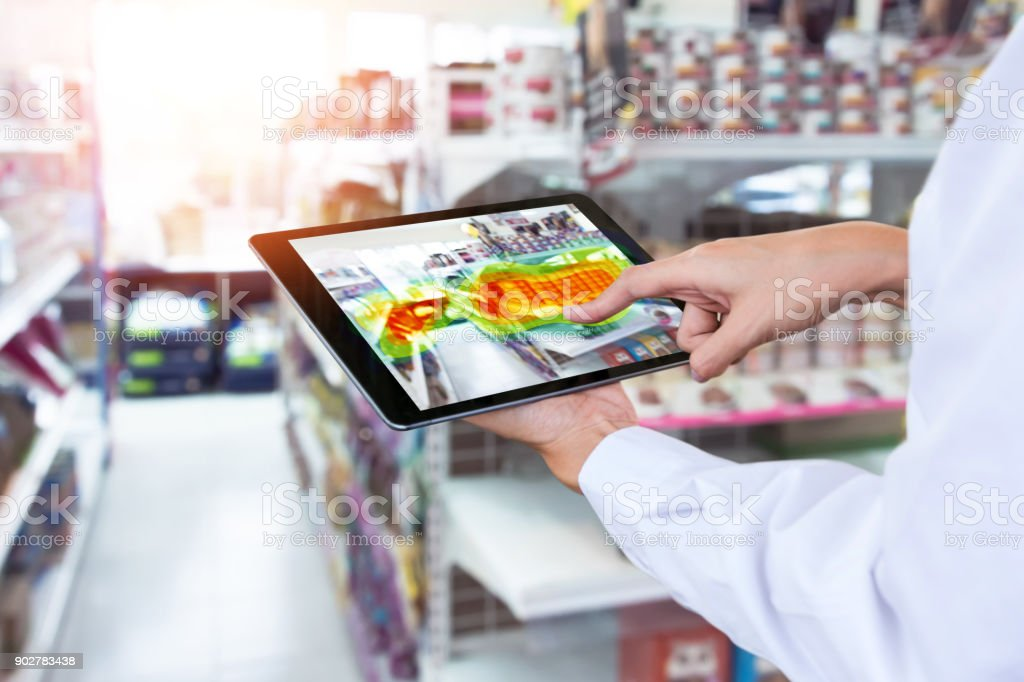 Heatmap Analytic in smart retail shop technology concept. Hand using smart phone with Pheat sense application check shoppers passed from any point in store. stock photo