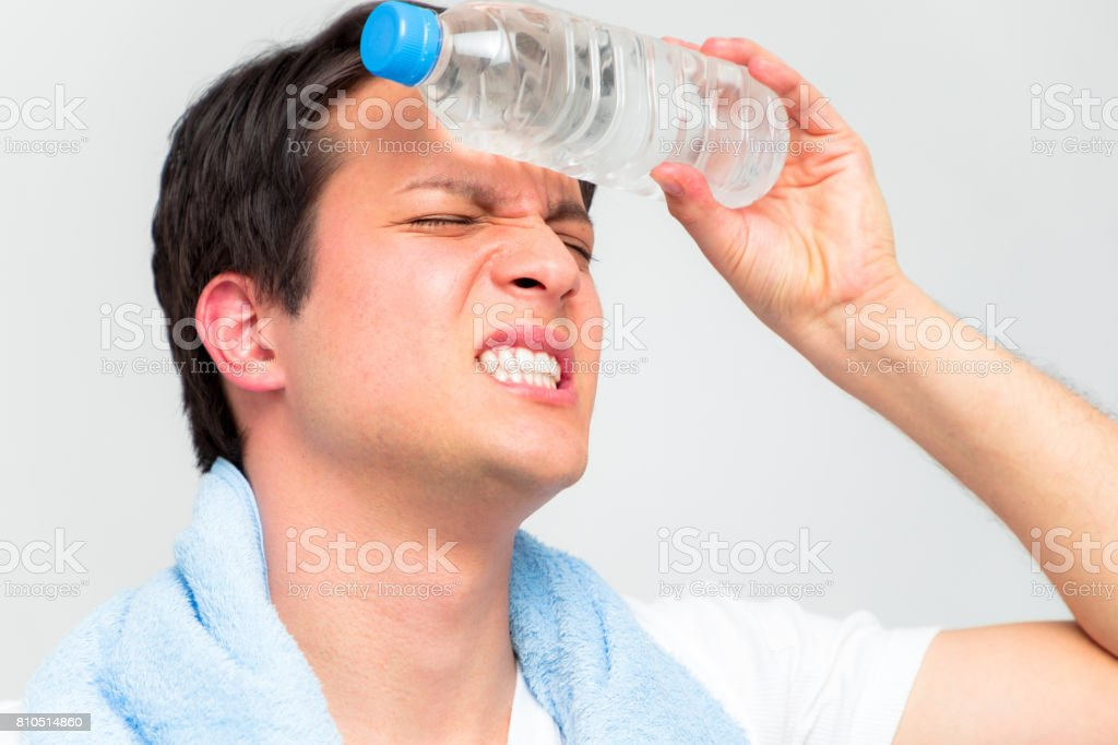 heatstroke concept. a young man cooling his head with a bottle of water. stock photo