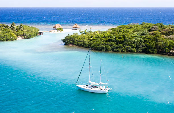 Heaven in Roatan A bird's eye view of a sailboat in the blue ocean of Roatan, Honduras honduras stock pictures, royalty-free photos & images
