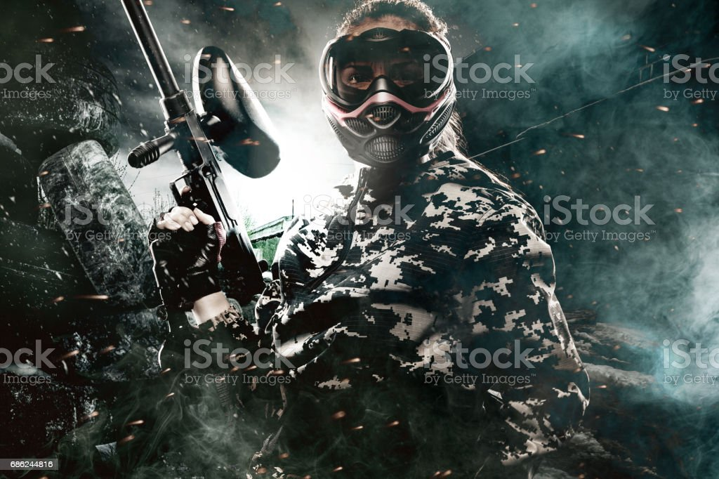 Heavily armed masked paintball soldier on post apocalyptic background. Ad concept. royalty-free