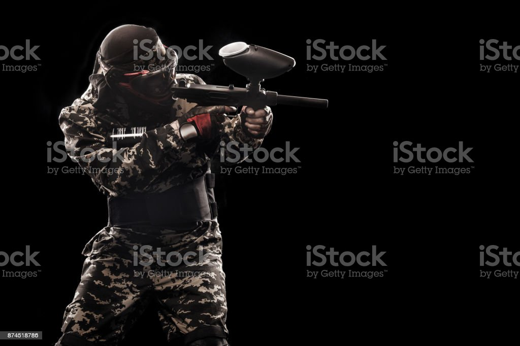 Heavily armed masked soldier isolated on black background. Paint ball and laser tag sport games. stock photo