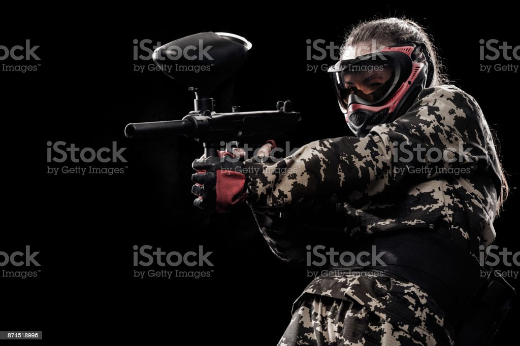 Heavily armed masked soldier isolated on black background. Paintball and lasertag sport games. stock photo