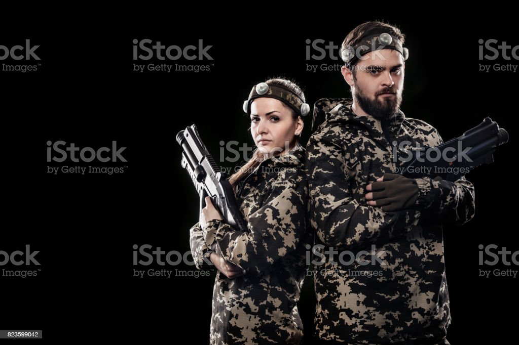 Heavily armed masked soldiers isolated on black background. Paint ball and laser tag sport games. stock photo