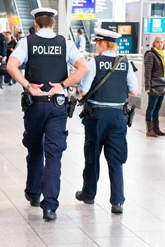 Frankfurt Main, Germany - April 27, 2016: A Policewoman and a policeman of the federal police patrolling heavily armed between the passengers in the lobby of terminal 1 at the International Airport Frankfurt Main, Germany.