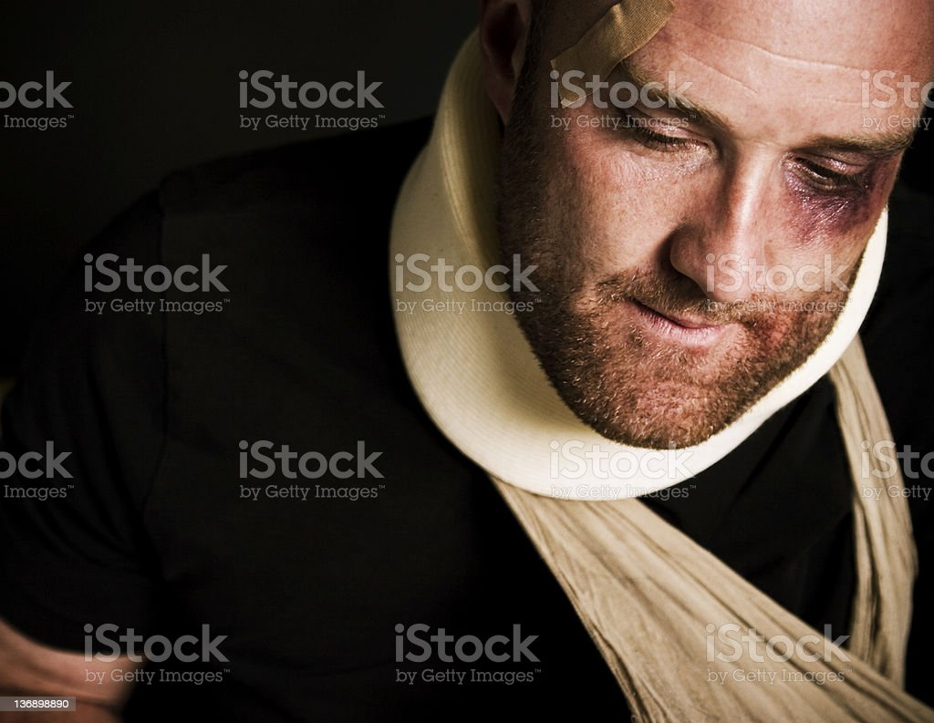 Heavily injured man with neck brace and arm sling stock photo