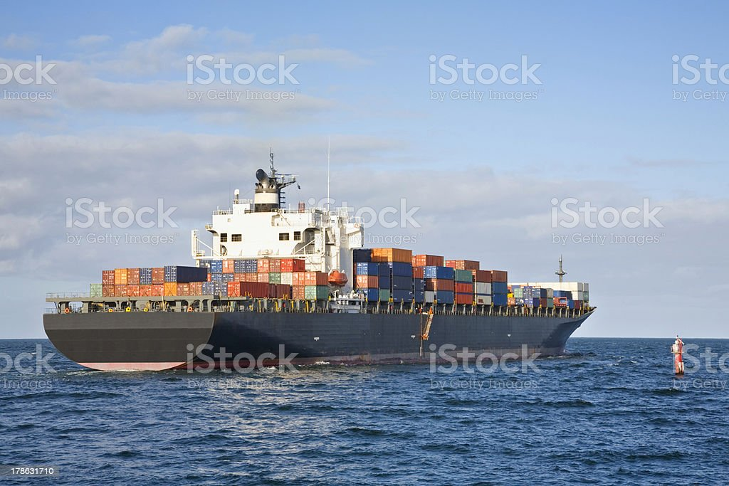 Heavily Laden Container Ship Leaving Port stock photo