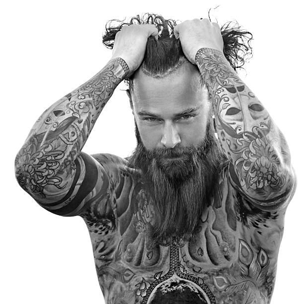 Heavily tattooed bare chested handsome male standing in warrior stance - foto stock